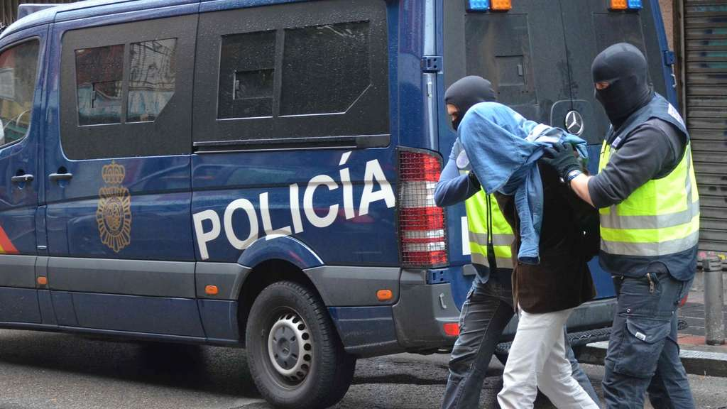 "This handout image released on November 3, 2015 by the Spanish Interior Ministry shows members of the Spanish Police leading one of three Moroccan men suspected to have links to the Islamic State jihadist group, who were aiming to carry out terror acts in Madrid. The three suspects, who are legal residents of Spain aged 26-29, were arrested in two neighbourhoods of the capital Madrid in the early hours, the interior ministry said in a statement.RESTRICTED TO EDITORIAL USE - MANDATORY CREDIT ""AFP PHOTO/ SPANISH INTERIOR MINISTRY"" - NO MARKETING NO ADVERTISING CAMPAIGNS - DISTRIBUTED AS A SERVICE TO CLIENTS - AFP PHOTO/ HO/ SPANISH INTERIOR MINISTRY"