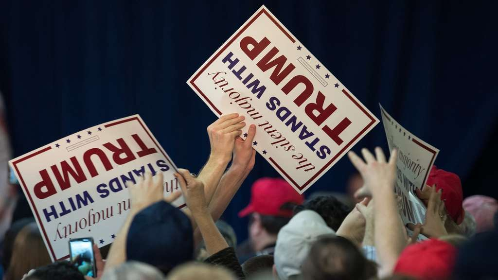 Supporters of US Republican presidential candidate Donald Trump hold up signs before he addresses a campaign rally in Manassas, Virginia, on December 2, 2015. AFP PHOTO/NICHOLAS KAMM