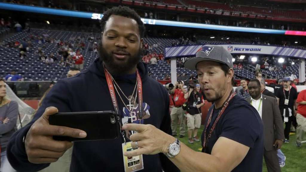 Michael Bennett (l) von den Seattle Seahawks und Mark Wahlberg machen ein ein Selfie in Houston. Foto: David J. Phillip