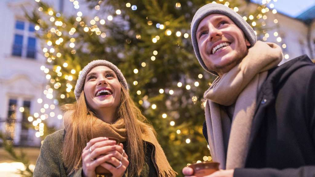 Laughing young couple drinking mulled wine at Christmas market model released Symbolfoto PUBLICATIO